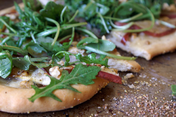 red pear, gorgonzola, + arugula pizza with pomegranate vinaigrette.