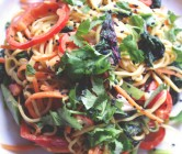rainbow noodle salad with amaranth leaves and spicy peanut dressing.